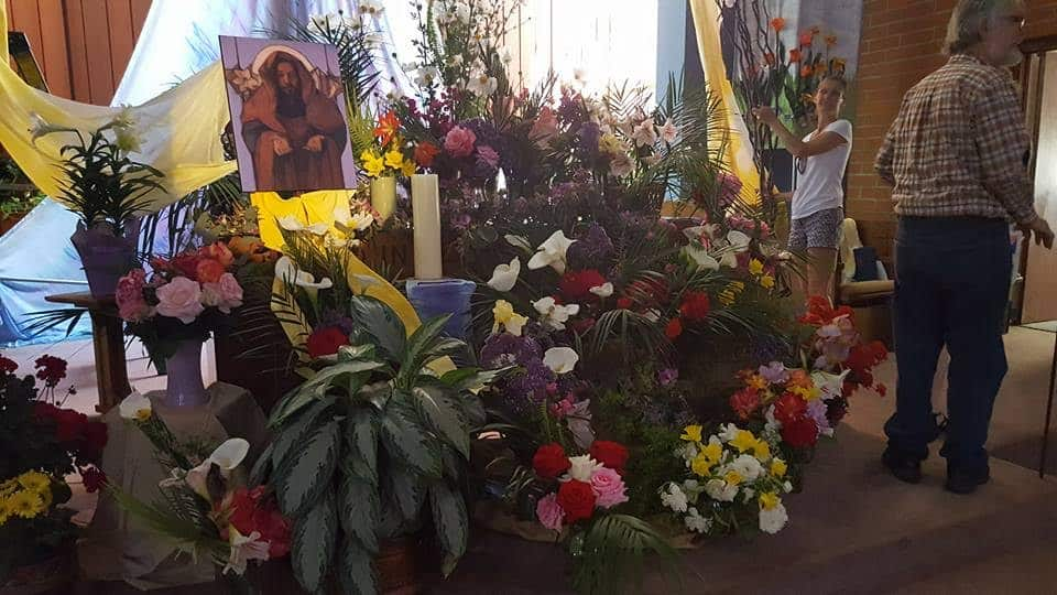 Lilies, roses, carnations, greenery, and other flowers and plants with candles, artwork, banners, and yellow veils being placed for Easter Sunday by a man wearing jeans and flannel and a woman in shorts and a white T shirt.