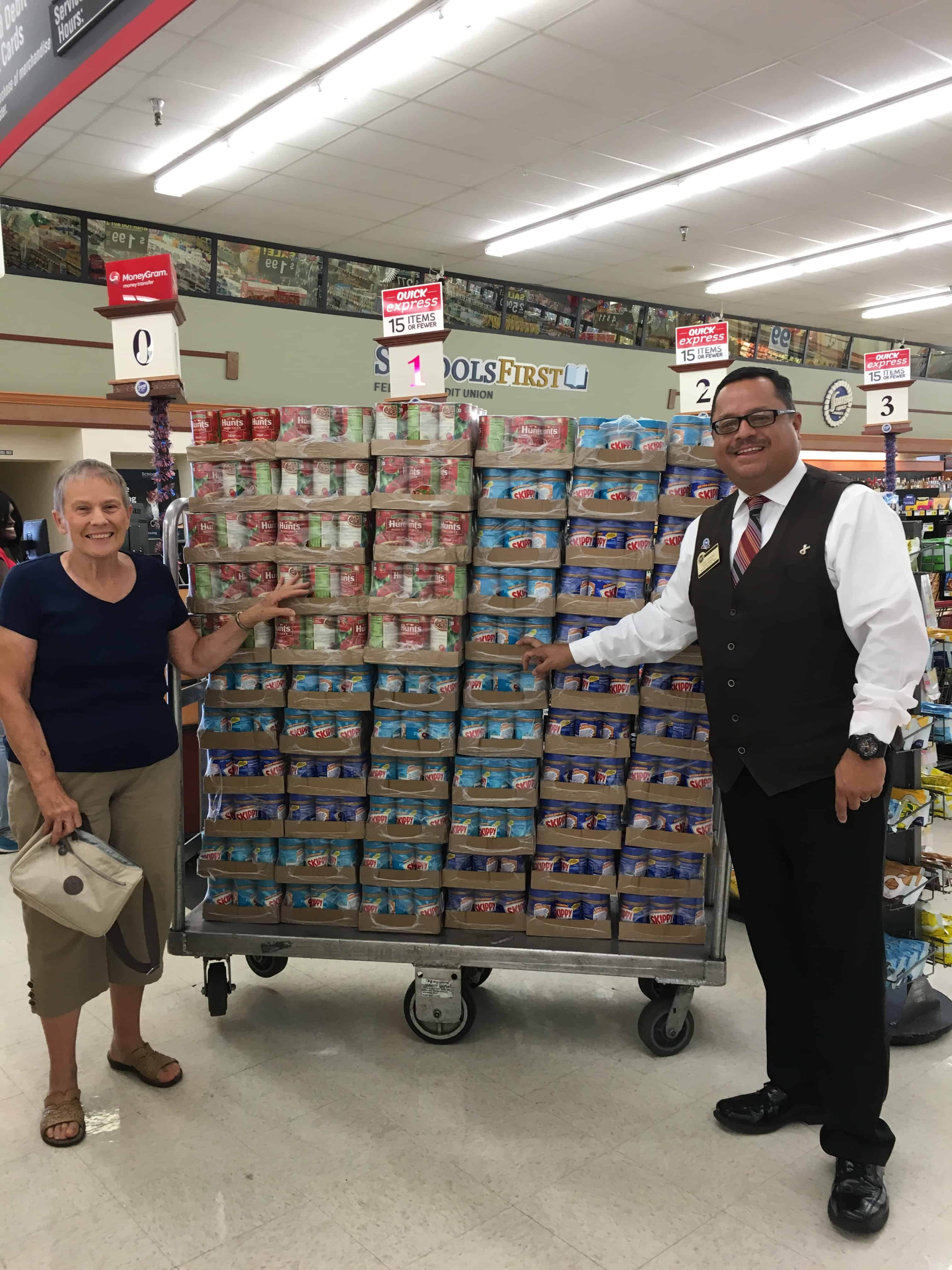 A woman and a man stand on each end of large stack of cases of peanut butter